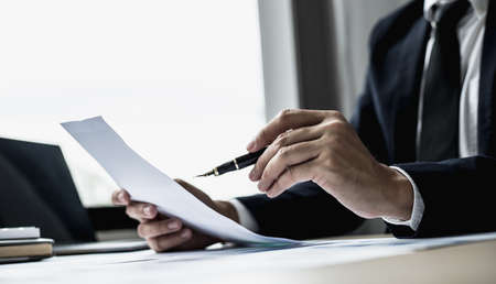 A businessman using a pen to point a pie chart on a document, he is reviewing financial documents from the finance department that summarizes monthly data for him to review before attending a meeting. Imagens