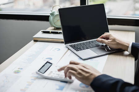 Man using laptop and pressing calculator, business man sitting in private office at his company, he runs a startup company, he's a young man starting a business. Management concept of startup company.