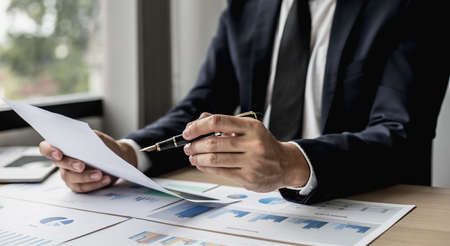 A businessman using a pen to point a pie chart on a document, he is reviewing financial documents from the finance department that summarizes monthly data for him to review before attending a meeting.