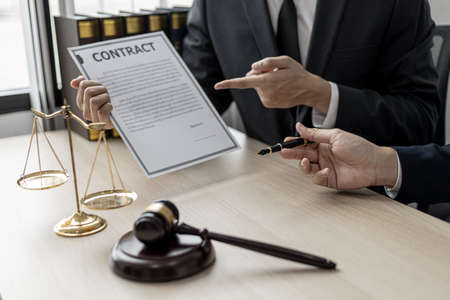 Two male lawyers are consulting together to draft a contract acknowledgment for their clients, they form partnerships to open a law firm. The idea of opening a law firm to accept the lawsuit. Stock Photo