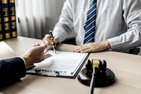 Attorneys or lawyers are advising clients in defamation cases, they are collecting evidence to bring charges against the parties for damages. The concept of defamation case counseling. Stock Photo