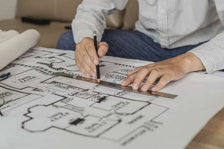 Architect uses a ruler to measure the blueprints of the houses he designed, designing the buildings according to the standards and the law, designing the houses according to the needs of the residents