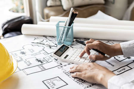 The architects pressed a calculator to calculate the area in a blueprint, designing the house according to the homeowner's requirements and according to the construction standards. Home design ideas. Standard-Bild