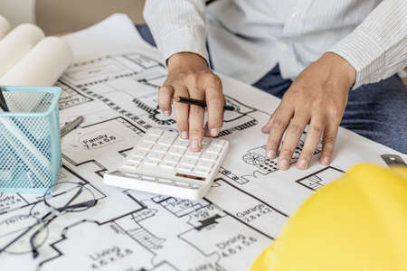 The architects pressed a calculator to calculate the area in a blueprint, designing the house according to the homeowner's requirements and according to the construction standards. Home design ideas.