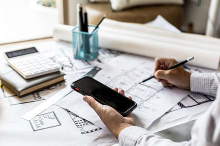 Architects review blueprints and view customer-submitted information on their smartphones, designing homes according to the homeowner's requirements and building standards. Home design ideas. Standard-Bild