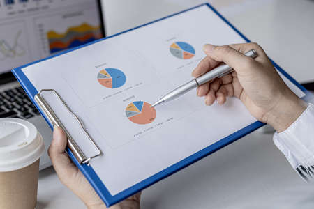 Businesswoman's hand holding a pen pointing at a bar chart on a corporate financial information sheet, the businesswoman examines the financial information provided by the finance department.