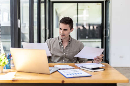 A businessman holding a sales document that the sales department summarizes, he looks displeased when he sees reports of falling sales, he shows signs of stress. Failed sales management concept.