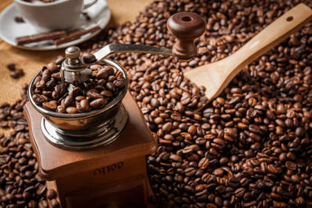 coffee grinder and beans background on sack and cup of coffee photo