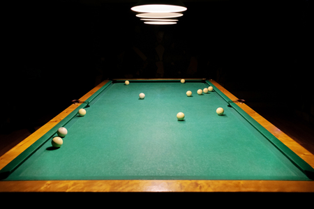 Ivory white billiard balls on a green pool table. There is space for your text or message. Russian billiards. The table is located in a dark room and lit by billiard lamps.