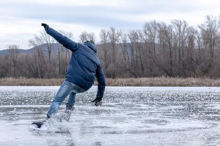 Patinando en el lago. Hombre cayendo mientras patina sobre hielo. Patinaje sobre hielo al aire libre en un estanque o río. Vista desde atrás. Patines de nieve de la dispersión en las fiestas.