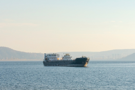 Old black cargo ship on the background of mountains. Oil tanker anchored. At the top there is a place for your text. Stock Photo