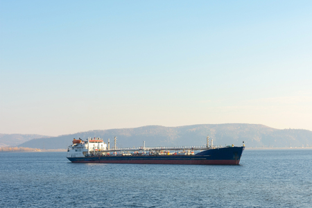 Cargo ship on the background of mountains. Oil tanker anchored. At the top there is a place for your text.