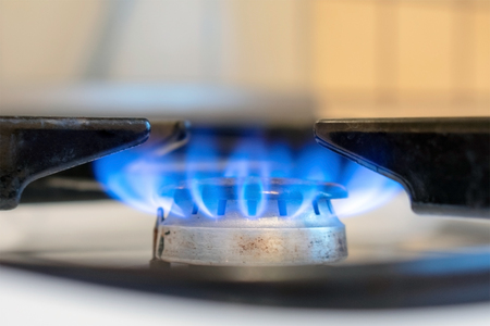 Old white kitchen stove cook with blue flames burning. Household gas stove. Can be a source of fire or explosion. Possible leakage and gas poisoning.