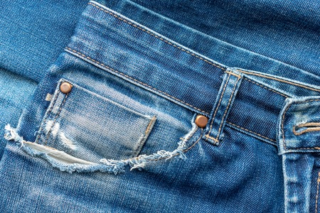 Close-up of old torn pocket blue jeans. Texture or background.