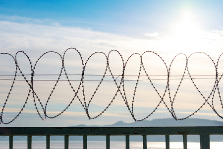 Barbed wire on a metal fence. Behind the fence is a blue sky with feathery clouds. In the lower part you can see of the mountains and river. Back light from the sun. The bright sun is located in the upper right part.