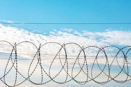 Barbed wire against a blue sky with feathery clouds. Theres room for your text.