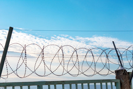 Barbed wire on a metal fence. Behind the fence is a blue sky with feathery clouds. You can see the pillars on which is attached Spiral Bruno. 스톡 콘텐츠