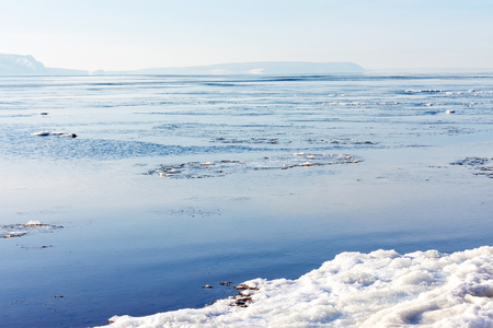 Beautiful winter or spring landscape. Breaking ice on the river. In the background in the distance you can see the mountains covered with fog. Sunlight breaks through the clouds in the blue sky and reflects off the water. Stock Photo