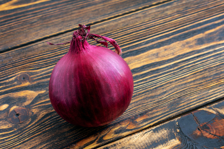 Big red onion close up on brown wooden background.
