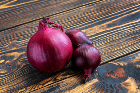 Red onion close up on brown wooden background. One large onion, two smaller ones. Stock Photo