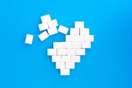 Broken heart from sugar cubes, blue background. The concept of problems associated with high blood sugar and diabetes. Sugar addiction. Concept of overeating simple carbohydrates and heart problems.