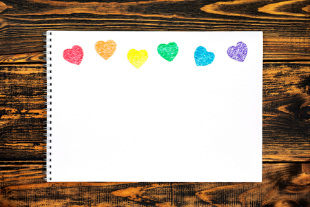 White card with colored hearts cut from paper. Hearts located on top and painted in the colors of the flag LGBT. There's room for your text. Concept of LGBT. Top view.