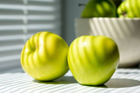 Two green apples on the table next to the window. In the background, a bowl of apples. Illuminated by sunlight passing through the closed blinds. photo in light colors.
