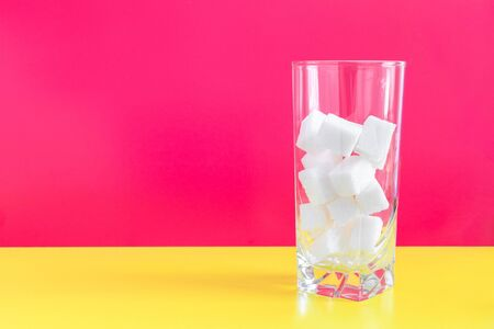 White refined pressed cubes sugar in the glass on pink and yellow background. The concept of high sugar content in beverages. copy space. Reklamní fotografie
