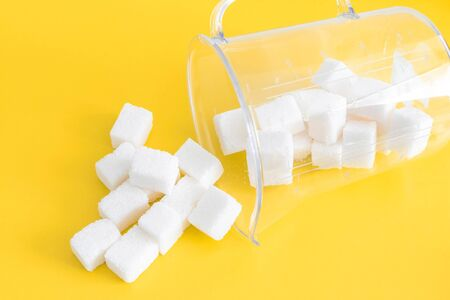 refined sugar on a bright yellow background in a measuring glass. Lies on a side of and sugar to Wake up. top view. concept of the harms of simple carbohydrates, excessive consumption of sugar in food Banco de Imagens