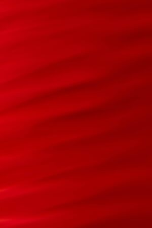 Deep red abstract background. Volumetric wavy texture with varying degrees of brightness and illumination. vertical photography.