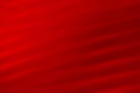 Deep red abstract background. Volumetric wavy texture with varying degrees of brightness and illumination. Stock Photo