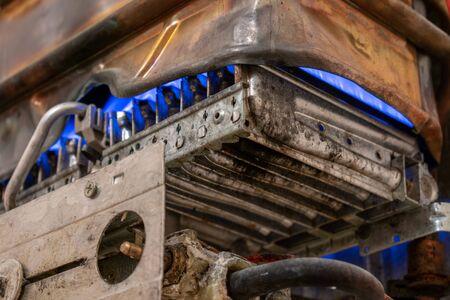 Oude versleten koperen gasboiler zonder beschermende behuizing. De ketel staat in de bedrijfsmodus. ondiepe scherptediepte. het concept van koolmonoxidelekkage en -vergiftiging. veiligheid van uitbuiting.