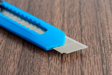 office knife on brown Desk. shallow depth of field. the concept of depression and suicide. Stock Photo