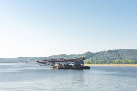 Floating crane on the river. Against the backdrop of beautiful summer mountains on a bright Sunny day. There's room for your text. Banco de Imagens