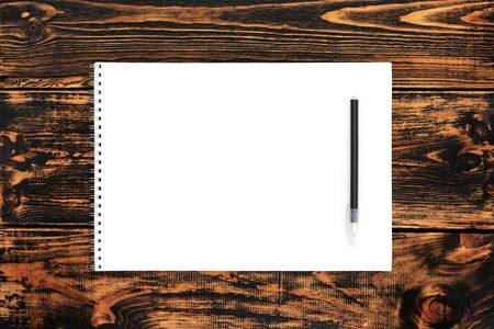 Blank paper and pen on the wooden background, top view, space for text or message. Blank paper mock-up. Banco de Imagens