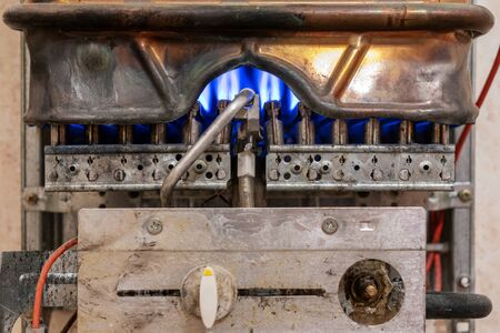 Old copper gas boiler without protective casing.The boiler is in operation mode.you can see the control panel of the boiler. the concept of carbon monoxide leakage and poisoning.safety of exploitation
