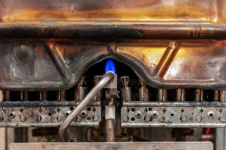 old worn copper gas boiler without protective casing. is in standby mode. close up photos. the concept of carbon monoxide leakage and poisoning. safety of exploitation. Banco de Imagens