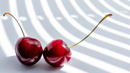 two cherry on white background illuminated by the rays of the sun from the window passing through the half-open blinds. fashion Studio photography. Banco de Imagens