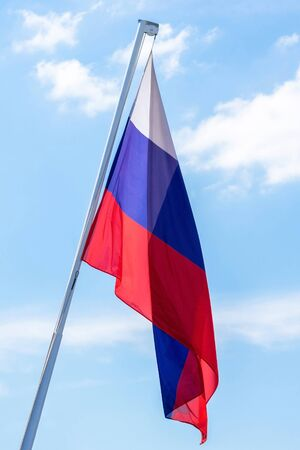 The flag of the Russian Federation in a quiet state against the blue sky. Vertical photo.