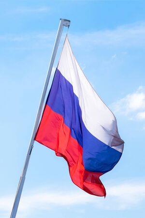 The flag of the Russian Federation is developing against the blue sky. Vertical photo. Banco de Imagens