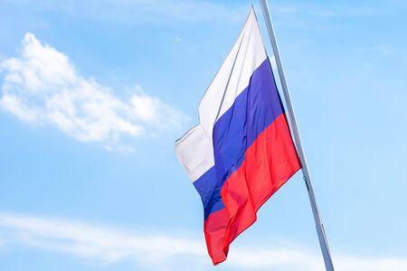 The flag of the Russian Federation is developing against the blue sky.