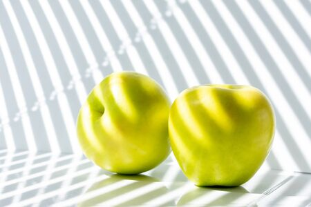 two green apples on the table. illuminated by sunlight passing through the closed blinds. beautiful photo with a small depth of field. photo in light colors.