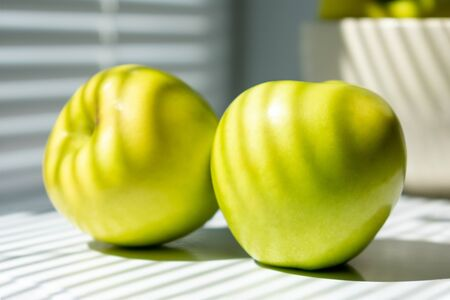 Two green apples on the table next to the window. In the background, a bowl of apples. Illuminated by sunlight passing through the closed blinds. close-up photo. photo in light colors. Banco de Imagens