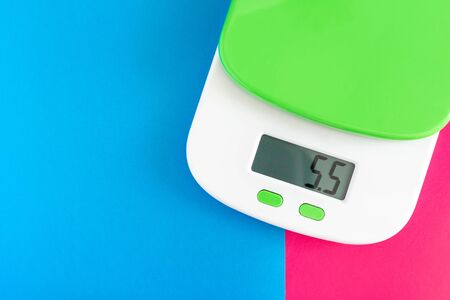Digital electronic kitchen scale on pink and blue background. copy space and place for your text.The concept of healthy eating and tracking the amount of food consumed.solving problems with overweight
