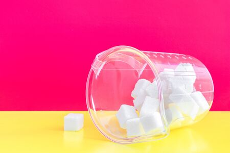 refined sugar on a bright pink and yellow background in a measuring glass.Lies on a side of and sugar to Wake up.the concept of the harms of simple carbohydrates,excessive consumption of sugar in food Banco de Imagens
