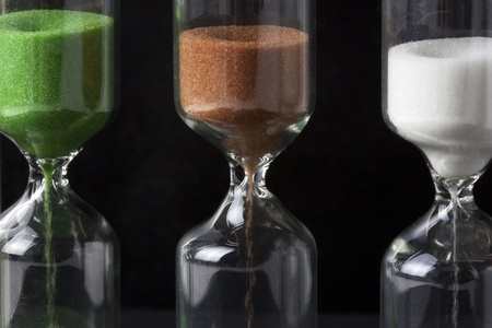 Three Coloured Hourglass on the black background
