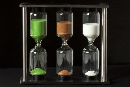 Tre färgTimglas på svart bakgrund