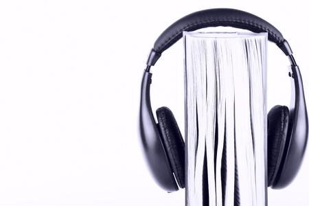 Book with headphones on the white background in blue key photo