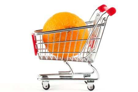 Buying healthy food. Shopping trolley with orange on white photo
