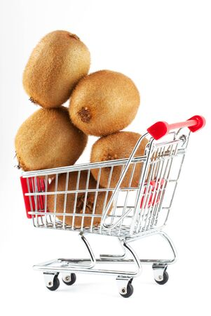 Buying healthy food. Shopping trolley with kiwi on white photo